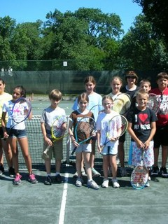 group of kids standing on tennis court